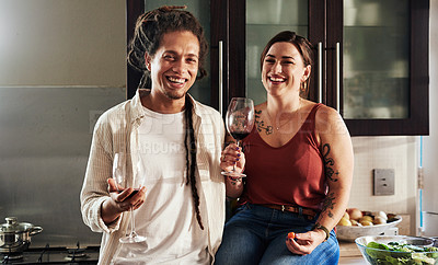 Buy stock photo Portrait of a cheerful young couple enjoying a glass of wine together while standing in the kitchen at home