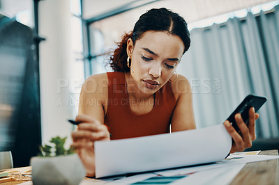 Buy stock photo Shot of a young designer making notes while using her cellphone at her desk