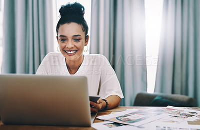 Buy stock photo Shot of a young businesswoman using a laptop and smartphone while working in her home office