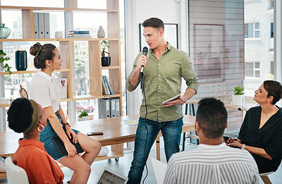Buy stock photo Cropped shot of a handsome young businessman using a mic to deliver his speech to his colleagues in the office