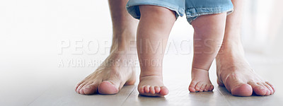 Buy stock photo Cropped shot of an unrecognizable little baby girl learning to walk with her father behind her at home