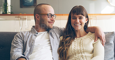 Buy stock photo Cropped shot of an affectionate young woman smiling while relaxing with her husband in their living room at home