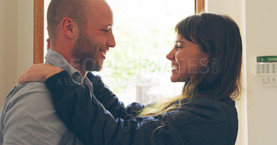 Buy stock photo Cropped shot of an affectionate young woman embracing her husband after arriving home during the day