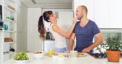 Buy stock photo Cropped shot of an affectionate young woman laughing while wiping her husband's mouth during breakfast  at home