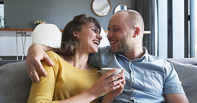 Buy stock photo Cropped shot of an affectionate young couple smiling at each other while relaxing in their living room at home