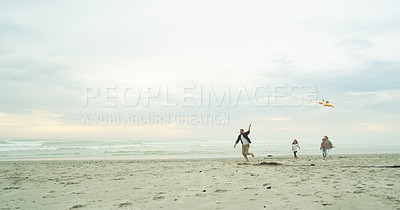 Buy stock photo Shot of a happy family flying a kite together at the beach