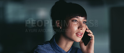 Buy stock photo Shot of a young businesswoman talking on a cellphone while working on a computer in an office at night