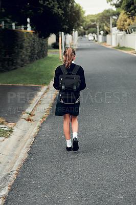 Buy stock photo Rearview shot of young schoolgirl walking to school