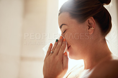 Buy stock photo Shot of an attractive young woman blowing her nose during her morning beauty routine at home