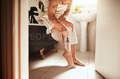 Buy stock photo Cropped shot of a woman shaving her legs in the bathroom at home