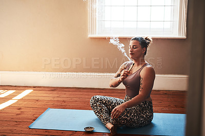 Buy stock photo Shot of a young woman burning a palo santo stick while sitting on a yoga mat at home