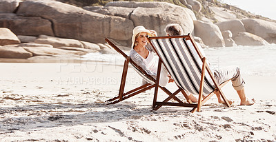 Buy stock photo Full length shot of an affectionate middle aged couple relaxing on loungers at the beach