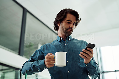 Buy stock photo Low angle shot of a young businessman using a cellphone while drinking coffee in an office