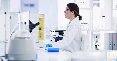Buy stock photo Shot of a young scientist working on a computer in a lab
