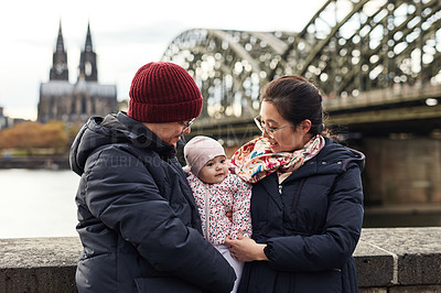 Buy stock photo Shot of a happy young family spending the day together outdoors in the city