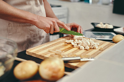 Buy stock photo Cropped shot of an unrecognizable woman chopping up fresh mushrooms while cooking inside her kitchen at home