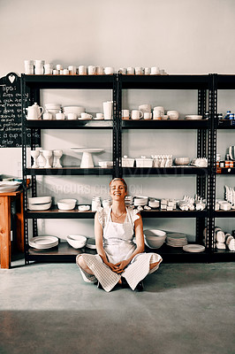 Buy stock photo Full length shot of an attractive mature woman sitting contently on the floor alone in her pottery workshop