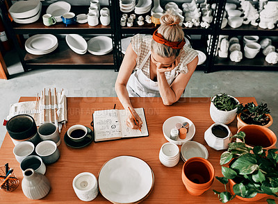 Buy stock photo High angle shot of an unrecognizable woman sitting and sketching in a notebook in her pottery workshop