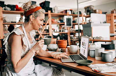 Buy stock photo Cropped shot of an attractive mature woman sitting alone and using her laptop in her pottery workshop while drinking coffee