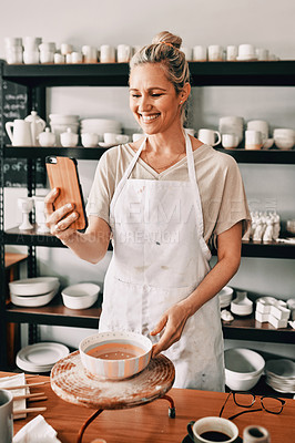 Buy stock photo Cropped shot of an attractive mature woman using her cellphone to take a selfie in her studio