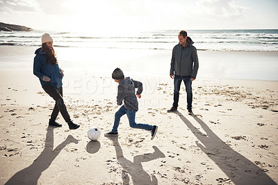 Buy stock photo Full length shot of a happy young boy playing soccer on the beach with his parents during a day out