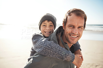 Buy stock photo Cropped portrait a handsome young man giving his son a piggy back while bonding together on the beach