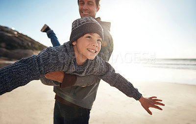 Buy stock photo Cropped shot of a handsome young man feeling playful and carrying his son during a day out on the beach