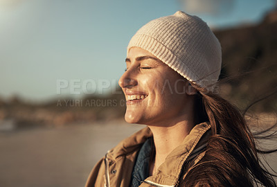 Buy stock photo Cropped shot of an attractive young woman standing alone and enjoying the sunset on the beach