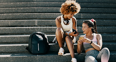 Buy stock photo Cropped shot of two attractive young sportswomen using their smartphones while taking a break outdoors