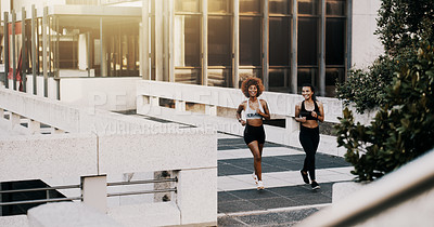 Buy stock photo Full length shot of two attractive young sportswomen jogging together outdoors in the city