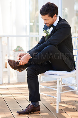 Buy stock photo Full length shot of a handsome young bridegroom sitting on a chair and tying his shoelaces on his wedding day
