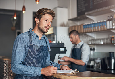 Buy stock photo Shot of a young man writing on a clipboard while working in a cafe with his colleague in the background