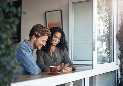 Buy stock photo Shot of a young couple looking at something on a cellphone while sitting in a cafe