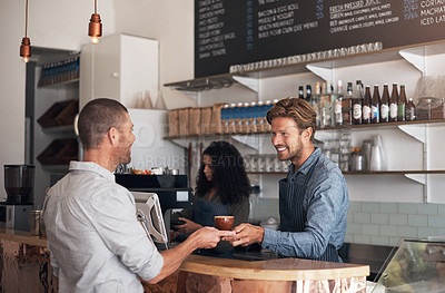 Buy stock photo Shot of a waiter serving a cup of coffee to a customer in a cafe