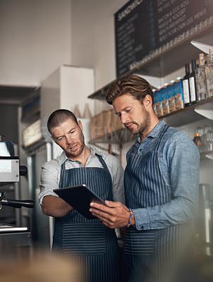 Buy stock photo Shot of two men working together on a digital tablet in a cafe