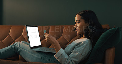 Buy stock photo Shot of an attractive young woman using her credit card and laptop to shop online while relaxing at home