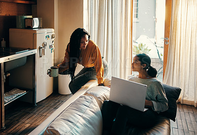 Buy stock photo Shot of two attractive young women drinking coffee and using a laptop while relaxing together at home over the weekend