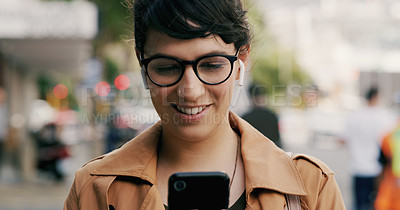 Buy stock photo Cropped shot of an attractive young businesswoman using a smartphone while swearing ear pods in the city during the day