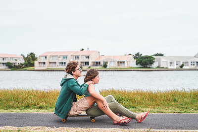 Buy stock photo Full length shot of two young children sitting on a skateboard together while bonding outdoors