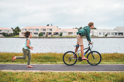 Buy stock photo Full length shot of a happy young boy riding his bicycle outside while his little sister runs behind him