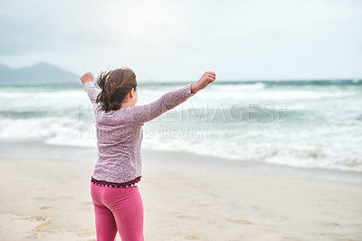 Buy stock photo Rearview shot of an unrecognizable girl standing on the beach with her arms raised during a day outdoors
