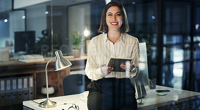 Buy stock photo Cropped portrait of an attractive young businesswoman smiling while using a digital tablet in a modern office at night