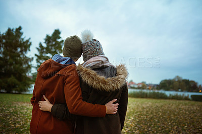 Buy stock photo Rearview shot of an unrecognizable couple looking at the view while standing in the park in late autumn