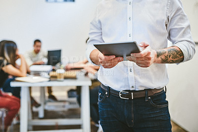 Buy stock photo Cropped shot of an unrecognizable businessman using a digital tablet in an office with his colleagues in the background