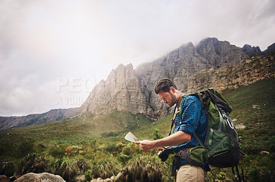Buy stock photo Shot of a young man using a map while hiking through the mountains