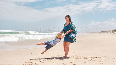 Buy stock photo Shot of an adorable little boy having fun with his mother at the beach