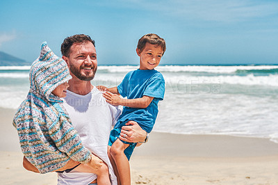 Buy stock photo Shot of two adorable little boys having fun with their father at the beach