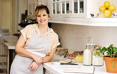 Buy stock photo Cropped shot of a beautiful young woman posing in her apron in her kitchen