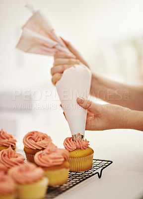 Buy stock photo Cropped shot of an unrecognizable woman piping icing onto her cupcakes