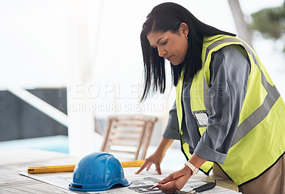 Buy stock photo Cropped shot of an attractive young female construction worker looking over plans on site